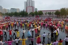 Beim Massentanz im Regen tanzen auch Touristen mit und alle haben sichtlich Spaß