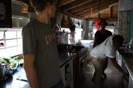 Jakob står i indgangen til køkkenet, der ligger i forbindelse med Lysthuset (the Gazebo), Kerry (vores kok og Mädchen für alles) med en hvide t-shirt og bsgved Poppie (fra Englnad/Jamaika)