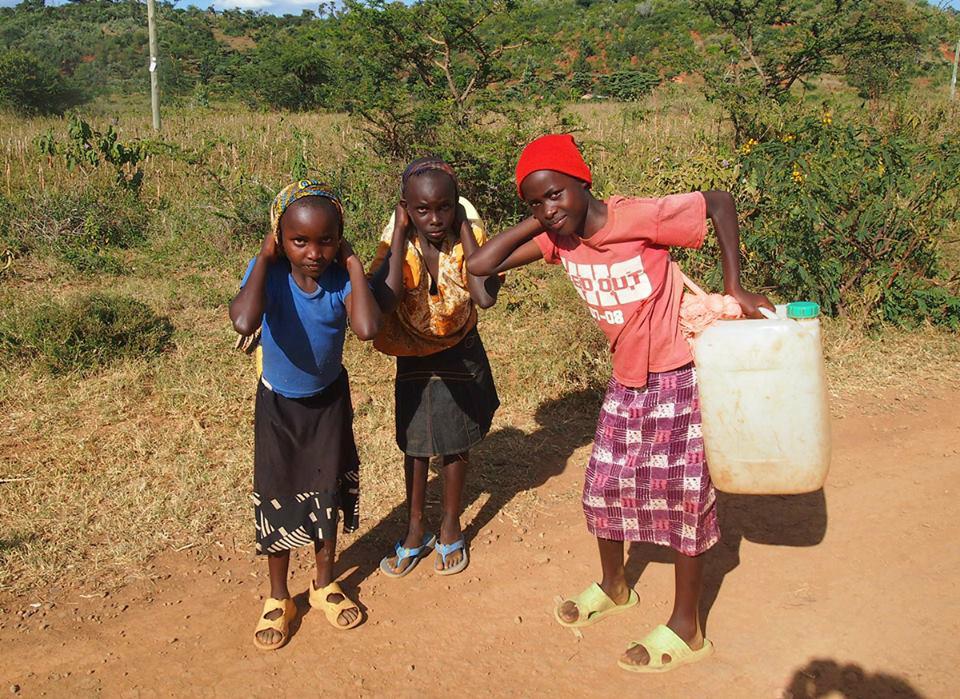 Kinder beim Tragen von Wasserkanistern