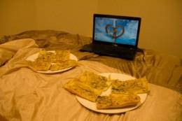 Kartoffelpizza vorm Laptop im Bett