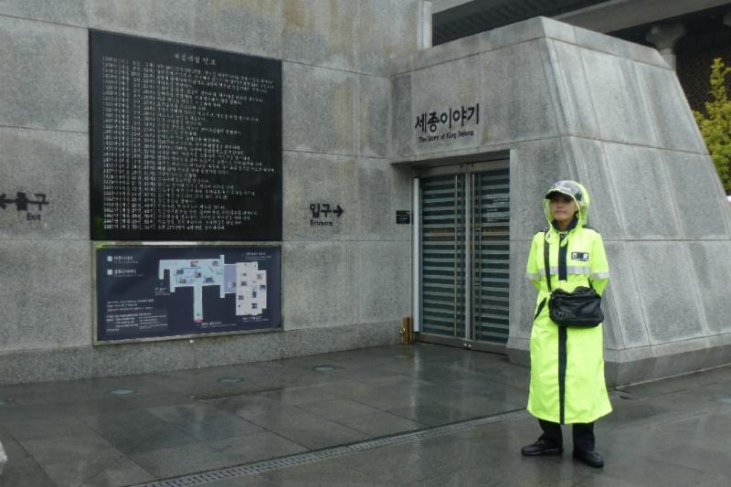 nette Polizistin im Regencepe vor Denkmal